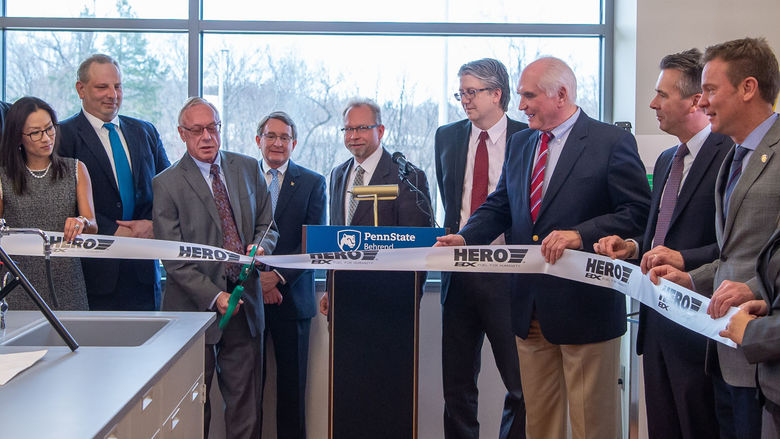 A group gathers to cut the grand-opening ribbon at a HERO BX lab at Penn State Behrend.