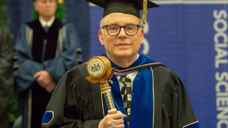 John Gamble carries the Penn State Behrend mace during a college commencement program.