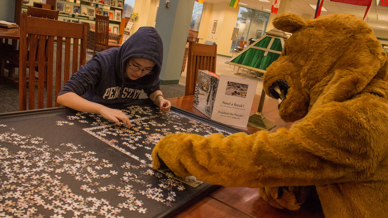 A college student builds a jigsaw puzzle with help from Penn State Behrend's Nittany Lion mascot.