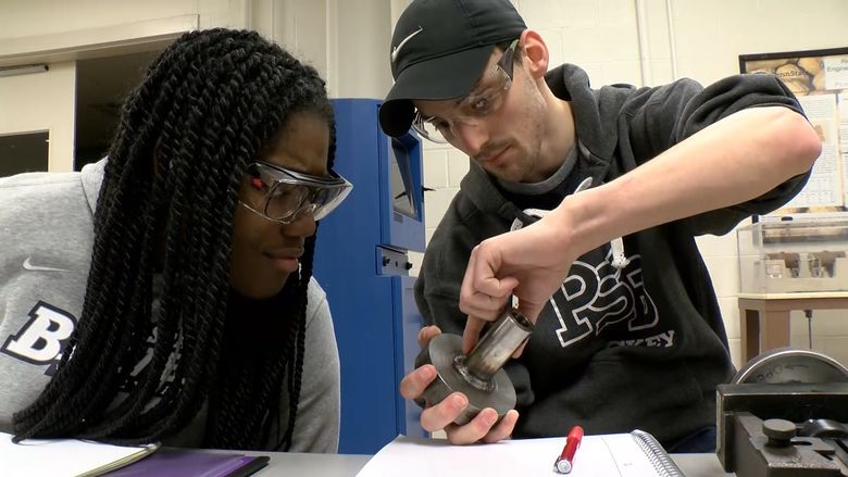 A pair of male and female MET students work together on a project.