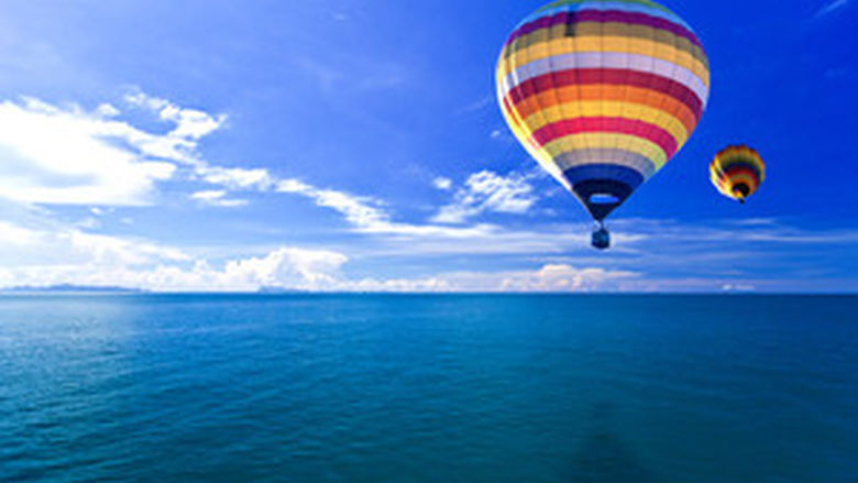A colorful hot air balloon floats above blue water against a blue sky.
