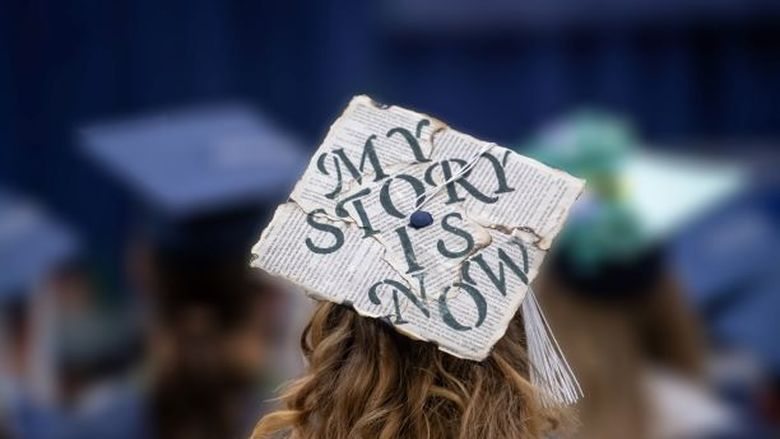 A close-up of a decorated mortarboard cap at a Penn State Behrend commencement program.