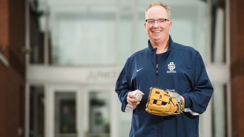 Penn State Behrend baseball coach Paul Benim stands in front of Junker Center.
