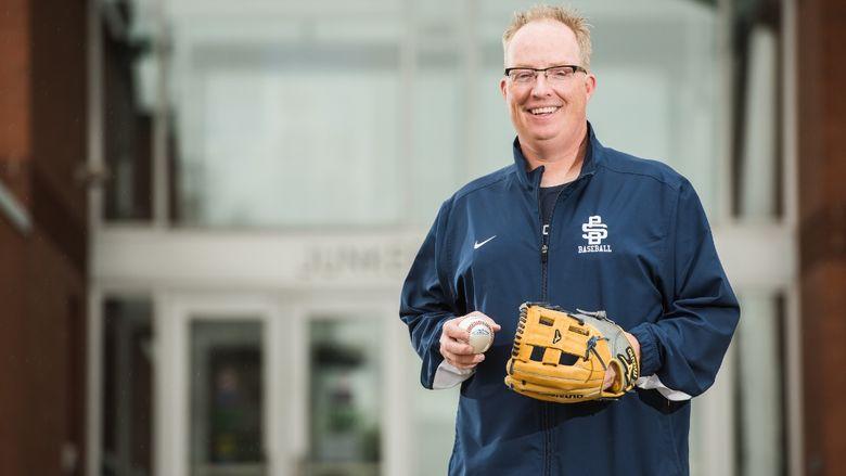 Penn State Behrend baseball coach Paul Benim stands in front of Junker Center.