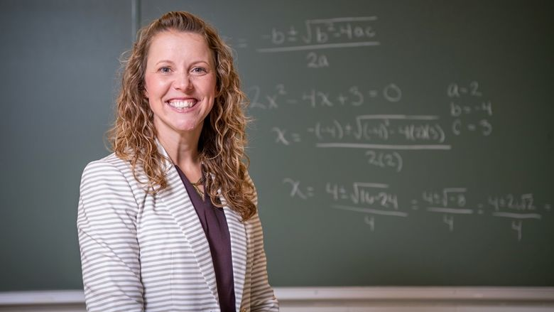 A Penn State Behrend professor explains a math problem while standing in front of a chalkboard.
