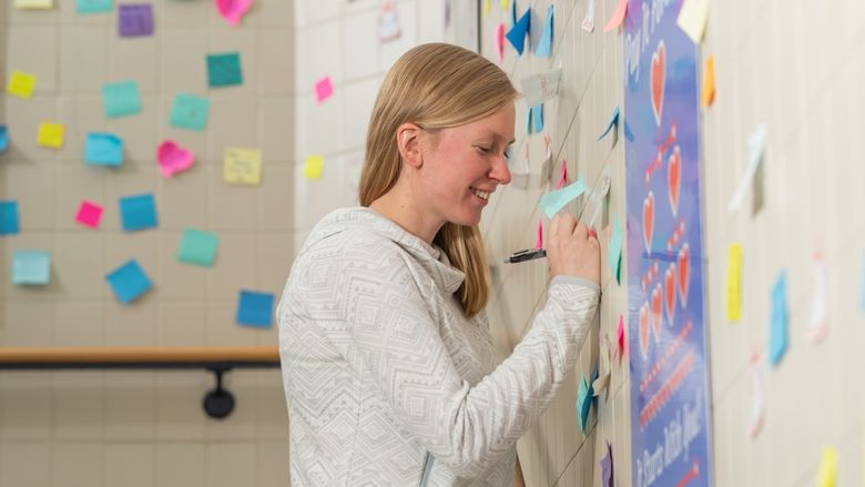Penn State Behrend alumna Ashlyn Kelly writes on a post-it note in the Reed Union Building stairwell.