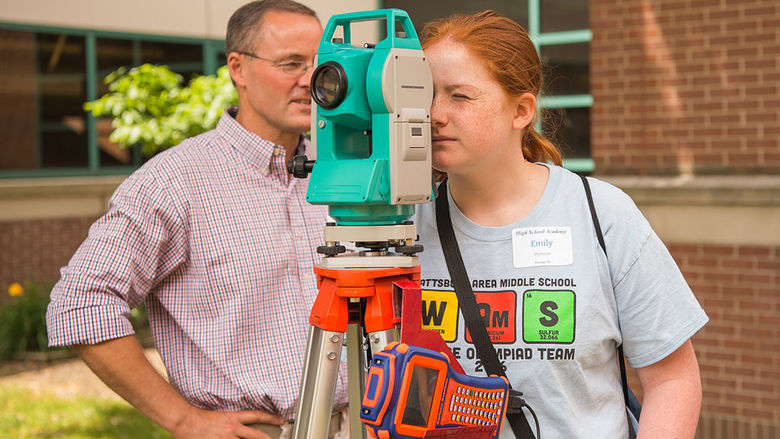 Professor shows student how to use surveying and data collection equipment.