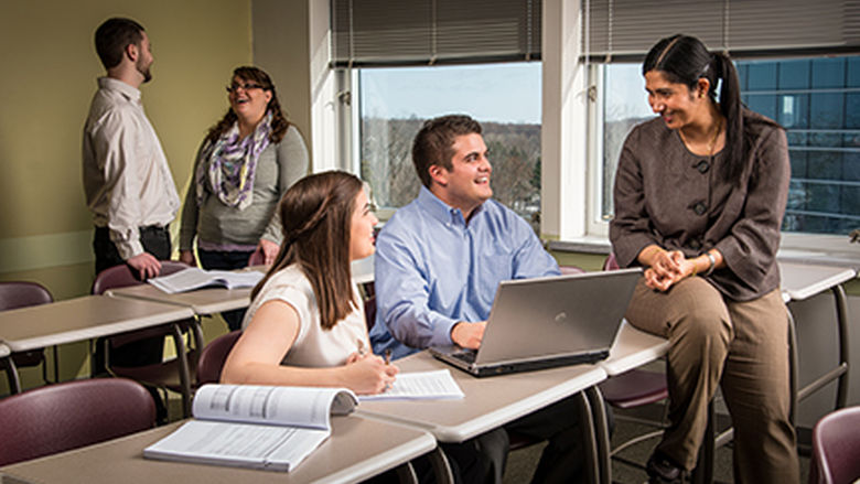 Four students talk with an instructor in Penn State Behrend's Master of Professional Accounting program.