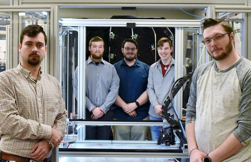 Five students pose near a large-scale 3D printer in Penn State Behrend's Innovation Commons lab.
