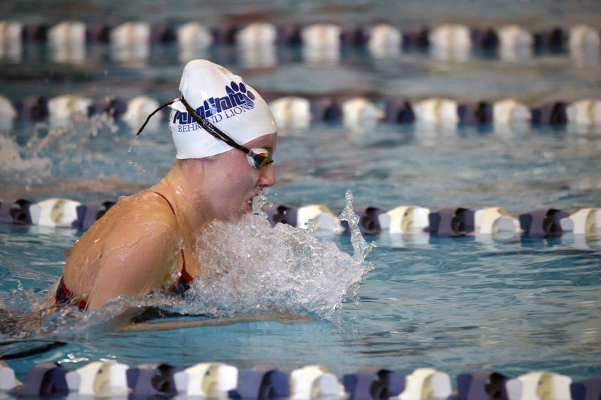 A Penn State Behrend swimmer competes in a race.
