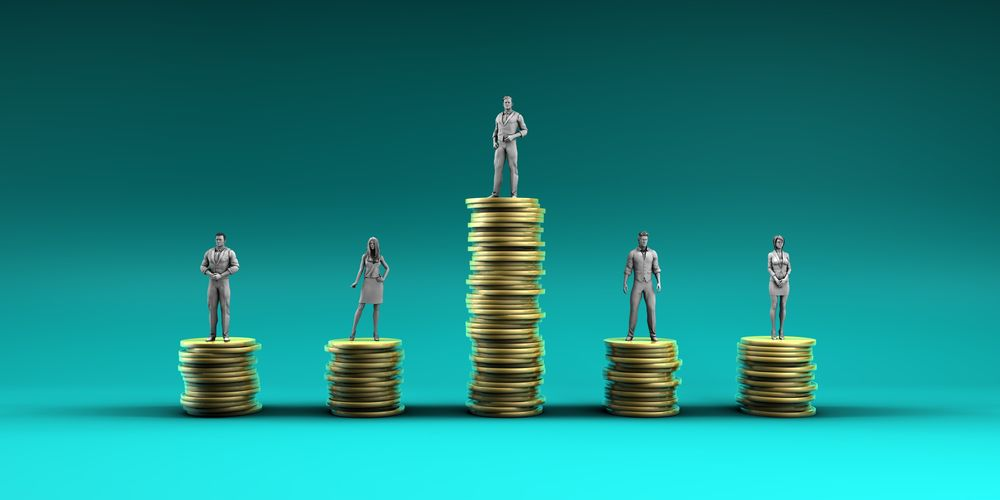 A series of figurines rest atop coins stacked to various heights to illustrate income inequality.
