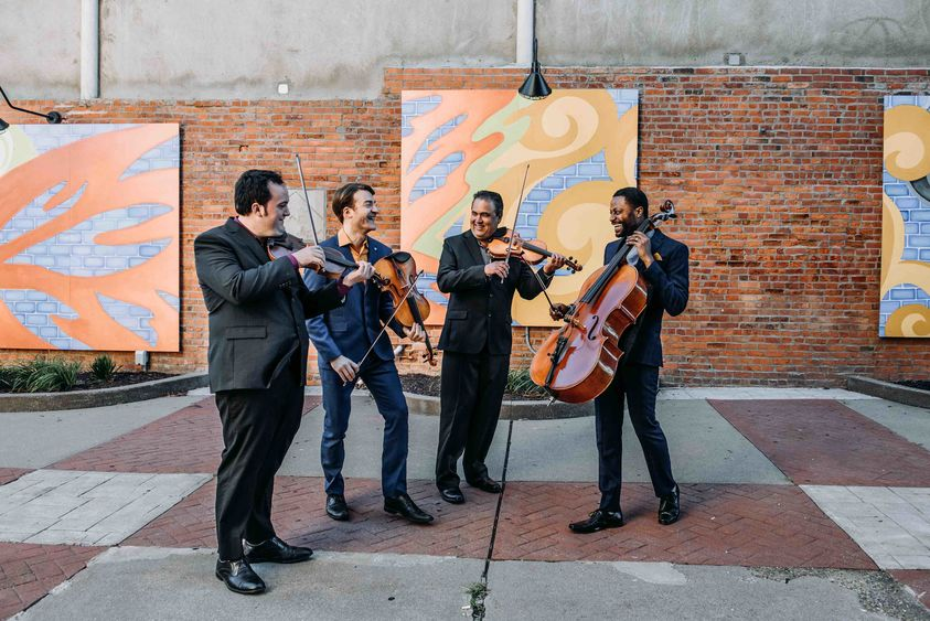 The Turtle Island Quartet performs in a street.