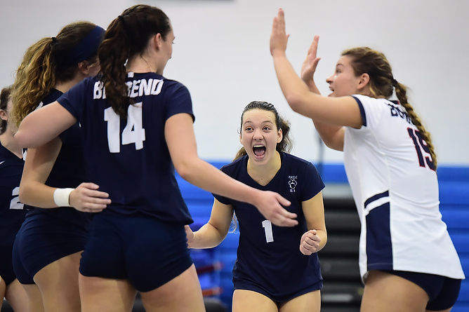 Penn State Behrend volleyball players celebrate after scoring a point.