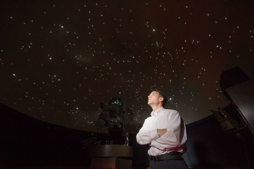 Jim Gavio, director of Yahn Planetarium, looks up at the starfield on the planetarium's ceiling.